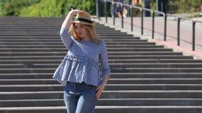 美丽白肤金发在城市楼梯穿上草帽并且送空气亲吻 股票视频