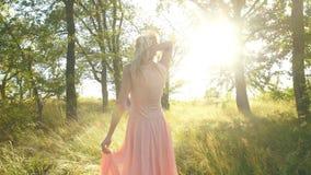 美丽白肤金发在桃色的步行礼服在森林和获得乐趣