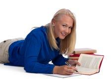 美丽白肤金发执行她的家庭作业学员 免版税库存图片