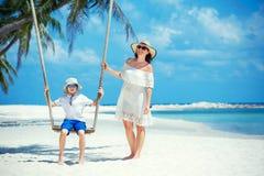 年轻美丽的一个热带海滩的妇女摇摆的儿子,酸值Phangan海岛 泰国 库存图片