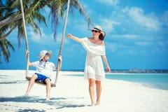 年轻美丽的一个热带海滩的妇女摇摆的儿子,酸值Phangan海岛 泰国 库存照片