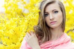 美丽的一件桃红色夹克的甜心典雅的女孩在与黄色花的灌木附近 库存照片