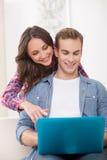 美丽的丈夫和妻子使用一台膝上型计算机 免版税库存照片