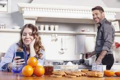 美丽的丈夫早餐为一个乏味妻子做准备 库存图片