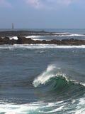美丽的不列塔尼的波浪和灯塔在背景中 库存图片