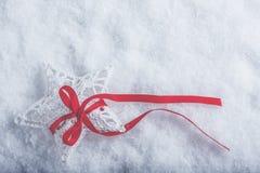 美丽的不可思议的葡萄酒白色星栓与在白色雪背景的一条红色丝带 冬天和圣诞节概念 免版税库存图片