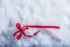 美丽的不可思议的葡萄酒白色星栓与在白色雪背景的一条红色丝带 冬天和圣诞节概念 库存图片
