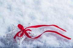 美丽的不可思议的葡萄酒白色星栓与在白色雪背景的一条红色丝带 冬天和圣诞节概念 免版税库存照片