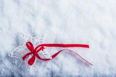 美丽的不可思议的葡萄酒白色星栓与在白色雪背景的一条红色丝带 冬天和圣诞节概念 免版税图库摄影