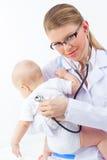 美丽的与听诊器的少妇儿科医生医生听的逗人喜爱的婴孩心脏。 免版税库存图片