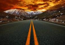 美丽的与沥青高速公路路的太阳上升的天空反对sno 库存图片