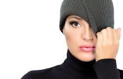 美丽的与盖帽的冬天女孩掩藏的眼睛。间谍 免版税库存图片