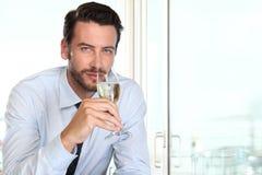 美丽的与迷人的神色和haught的人饮用的香槟 免版税图库摄影