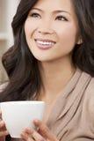 美丽的东方妇女饮用的茶或咖啡 库存图片
