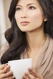 美丽的中国东方亚裔妇女饮用的茶或咖啡 免版税库存图片