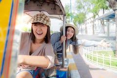 美丽的中国或日本妇女推进自动人力车和她的泰国朋友在她后坐 他们是亲密的朋友和 免版税图库摄影