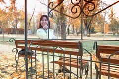 美丽的中年妇女坐长凳在公园 翠菊许多秋天的紫红色心情粉红色 妇女坐长凳在中间 库存图片