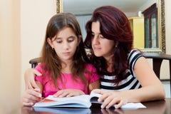 美丽的书女孩她的母亲读取 免版税图库摄影