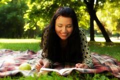 美丽的书女孩室外读取 免版税库存照片