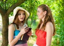 美丽的书愉快户外微笑二名妇女 免版税库存照片