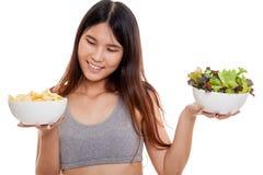 美丽的亚洲健康女孩沙拉和土豆片 免版税库存照片