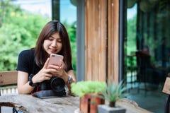 美丽的亚洲妇女藏品照相机在庭院里 免版税库存图片