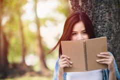 美丽的亚洲妇女读书笔记本 免版税图库摄影