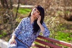 美丽的亚裔出现女孩坐长凳在公园和谈话在电话 免版税图库摄影