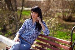 美丽的亚裔出现女孩坐长凳在公园和谈话在电话 免版税库存照片