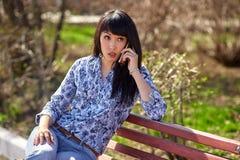 美丽的亚裔出现女孩坐长凳在公园和谈话在电话 免版税库存图片