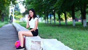 年轻美丽的亚裔女孩使用电话,在绿色公园叫并且谈话 股票视频