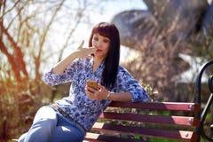 美丽的亚裔女孩在手中坐长凳在有非常惊奇的电话的公园 库存图片