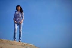 美丽的亚裔女孩在蓝色牛仔裤站立反对蓝天 免版税图库摄影