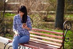 美丽的亚裔女孩坐一条长凳在读消息的公园在电话 免版税库存照片