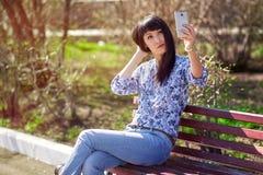 美丽的亚裔女孩坐长凳在公园,做selfie在智能手机 免版税库存图片