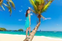 年轻美丽的亚裔女孩用在棕榈树的椰子在一个热带海滩 库存照片