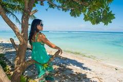 年轻美丽的亚裔女孩画象在树荫下在树下坐看海洋的热带海滩 免版税库存图片
