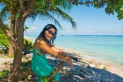 年轻美丽的亚裔女孩画象在树荫下在树下坐看照相机的热带海滩 免版税图库摄影