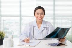 美丽的亚裔女性在诊所的医生审查的X-射线报告 库存照片