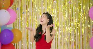 美丽的亚裔妇女享用与在金子闪烁背景的五彩纸屑 影视素材