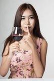 美丽的亚裔妇女使标志举行杯红葡萄酒平静 免版税库存照片