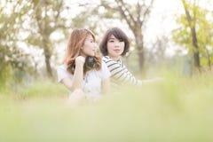 年轻美丽的亚裔妇女听的音乐和谈论 库存照片