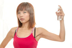 美丽的亚裔妇女喷洒的头发用水 库存图片