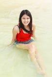 美丽的亚裔妇女坐海滩 库存图片