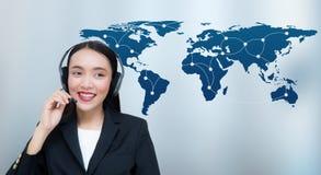 美丽的亚裔妇女微笑的顾客服务谈话在有世界地图通信的耳机 库存图片