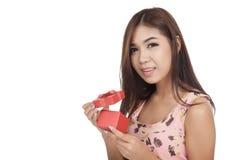 美丽的亚裔妇女打开红色礼物盒神色在照相机 免版税库存照片