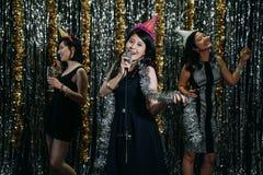 美丽的亚裔妇女爱音乐享受卡拉OK演唱 库存照片