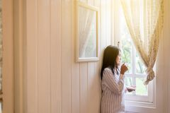 美丽的亚裔妇女画象拿着一杯咖啡并且在家看某事在窗口在早上,愉快和smil 免版税图库摄影