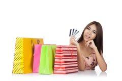 美丽的亚裔妇女满意对信用卡和购物袋 库存照片