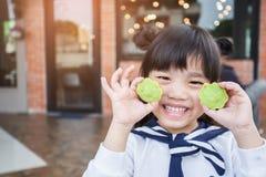 美丽的亚洲孩子画象感到愉快吃两个点心馅饼 库存照片